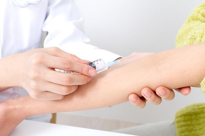 腕に静脈注射される女性